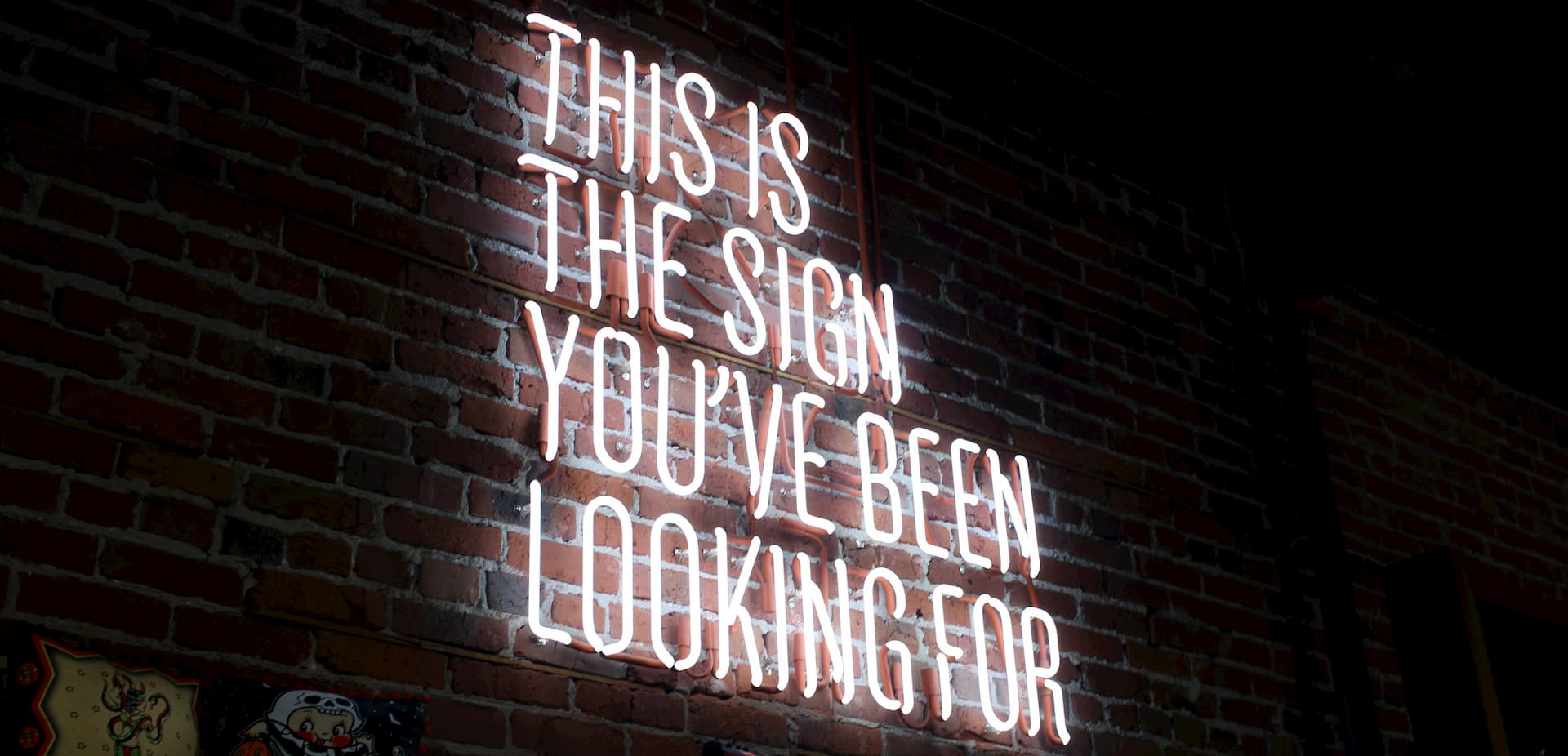 Neon sign on brick wall saying This is the sign you've been looking for